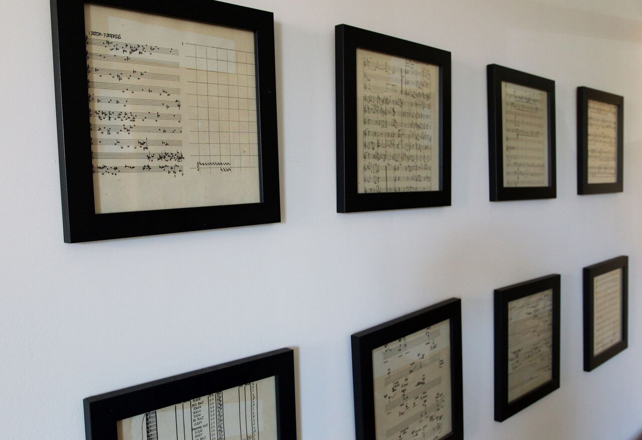 A wall filled with framed pages of scores by John Cage