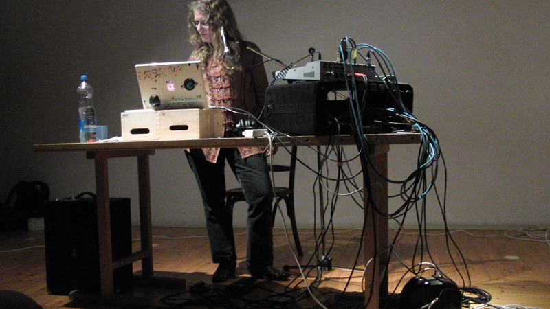 Dafna Naphtali creating music from her laptop which is connected to a bunch of cables hanging down from a table. (photo by Skolska/Prague)