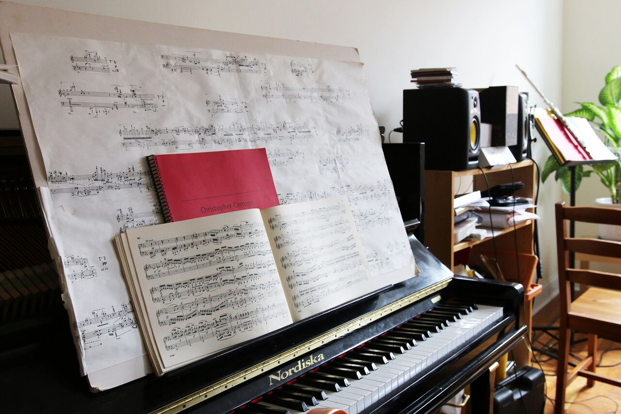 Three superimposed scores are propped up on Cerrone's piano, Stockhausen's Klavierstucke XI, an original composition, and a Beethoven sonata.
