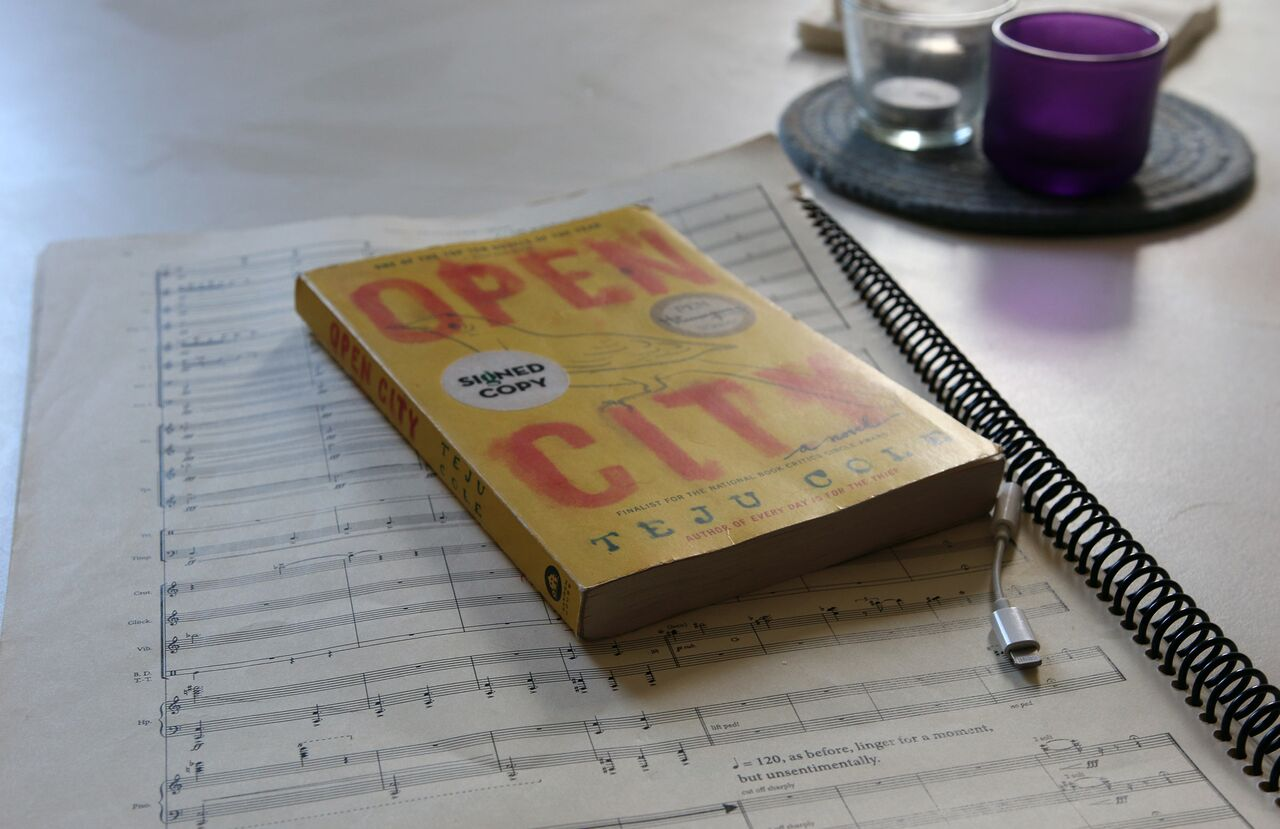 A paperback copy of Teju Cole's novel Open City rests on top of a page of Cerrone's music manuscript.