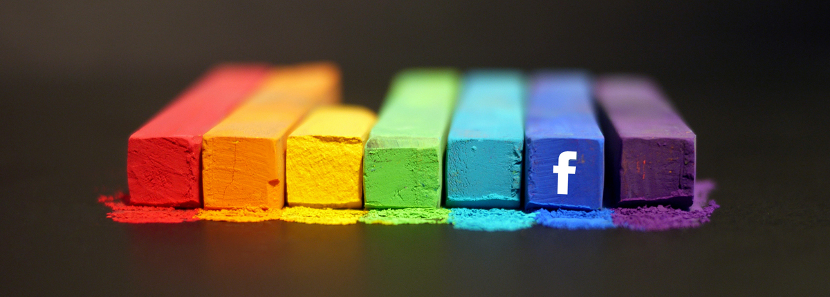 A group of seven rectangular box-shaped crayon sticks in different colors (from left to right: red, orange, yellow, light green, sky blue, dark blue, and purple); a white lower case f (the Facebook logo) appears on the front of the penultimate one (the one in dark blue).