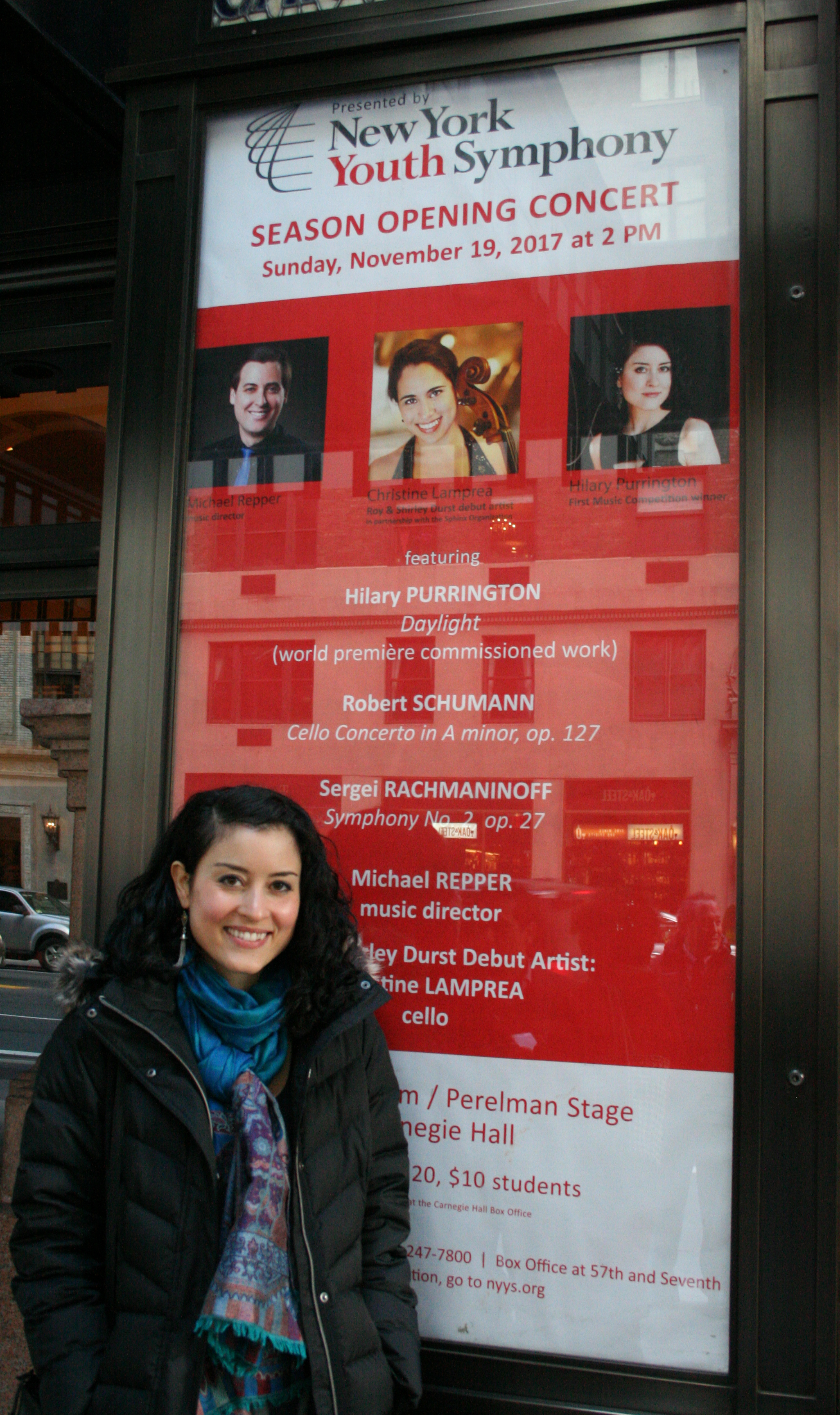 Hilary Purrington standing outside Carnegie Hall in front of the New York Youth Symphony November 19, 2017 Concert Poster featuring a photo of her and listing her world premiere performance.