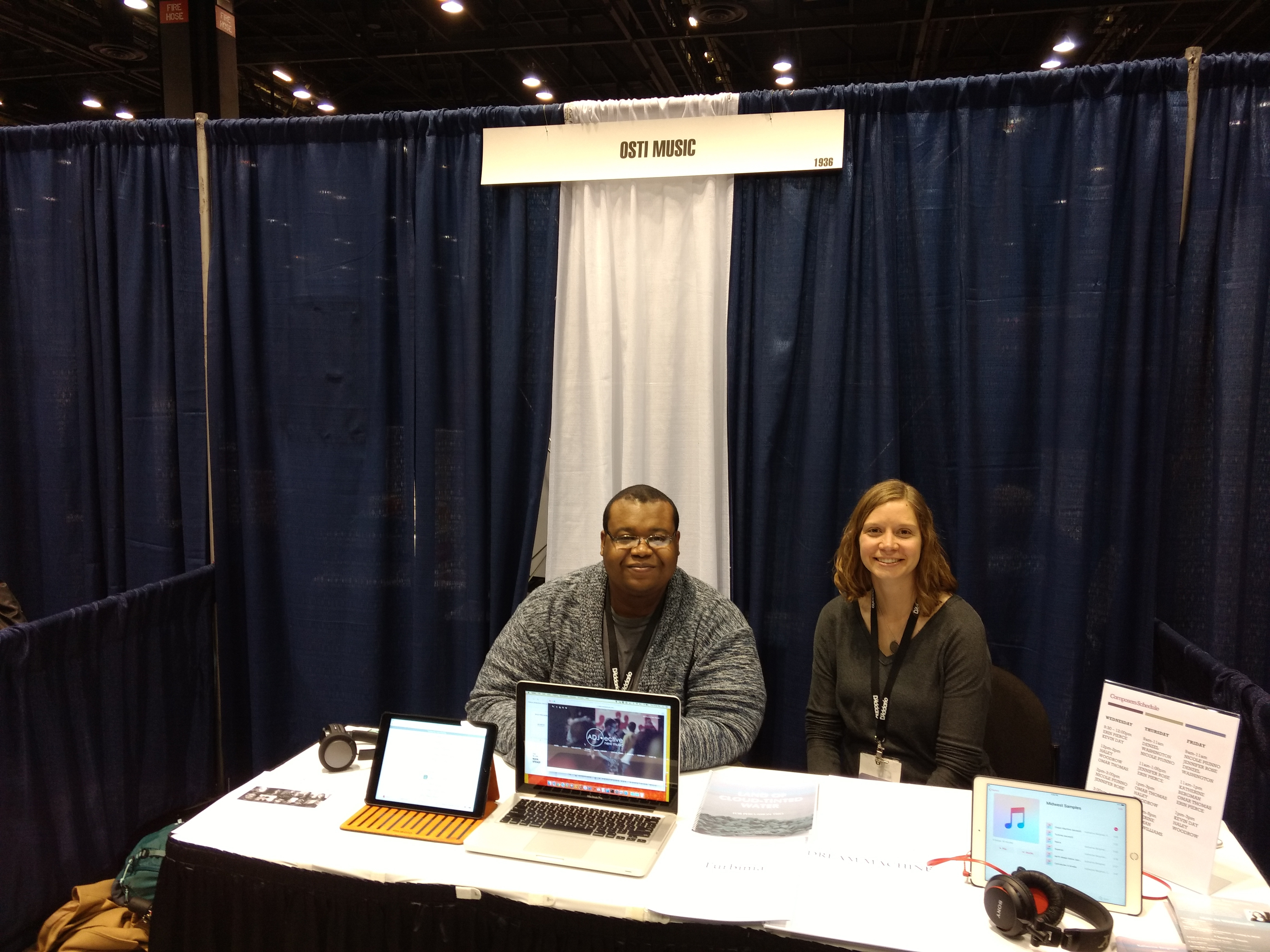 Evan Williams and Katherine Bergman at the Osti Music Booth with open laptops featuring their music.