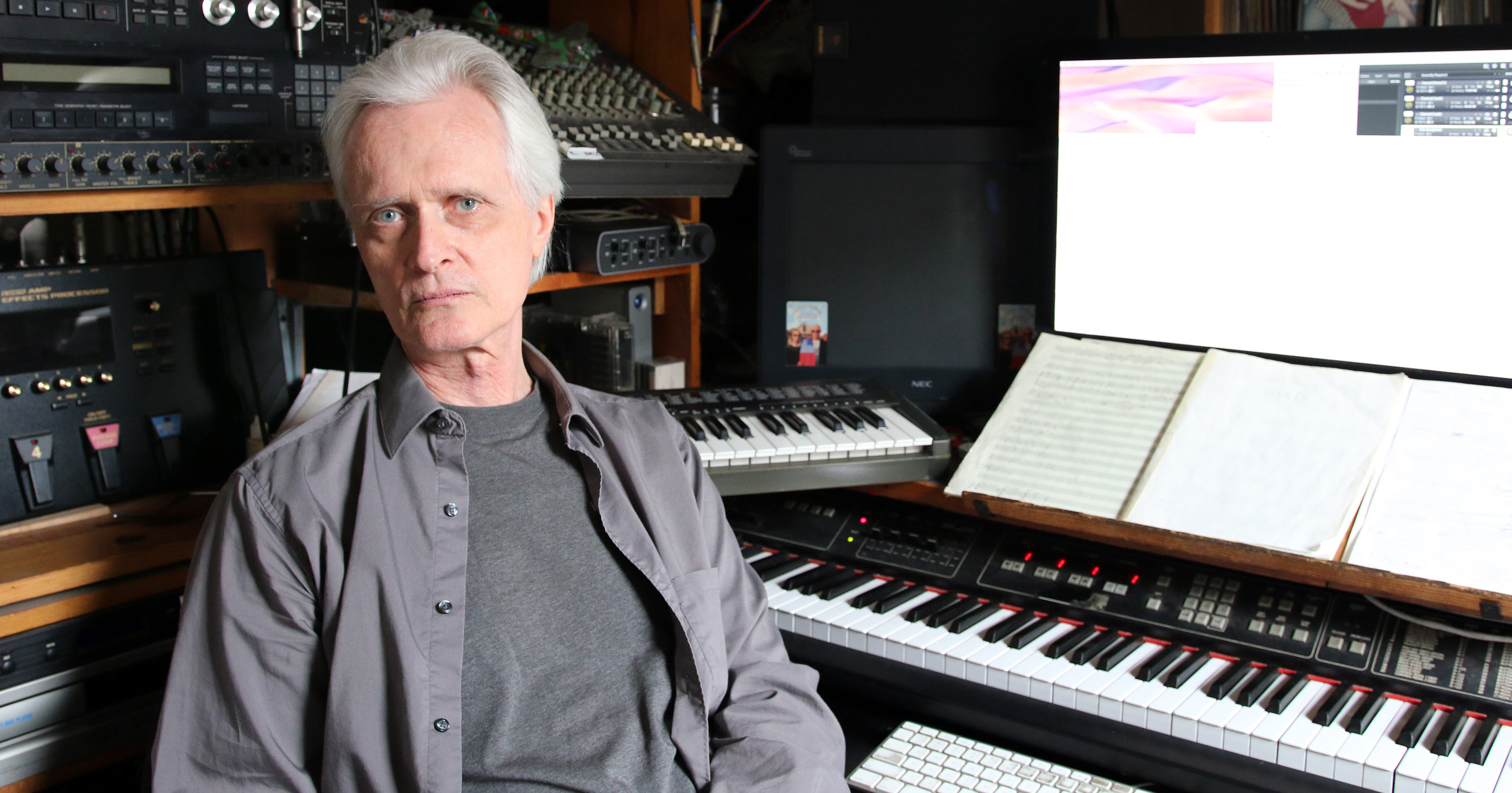 Scott Johnson in front of his work station with various electronic keyboards.