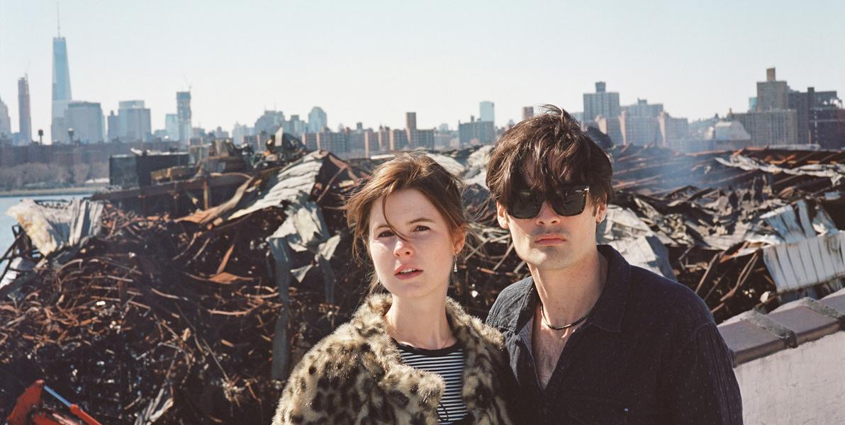 Rosalie Kaplan and Noah Kaplan standing in front of a dump near a river overlooking the Manhattan skyline.