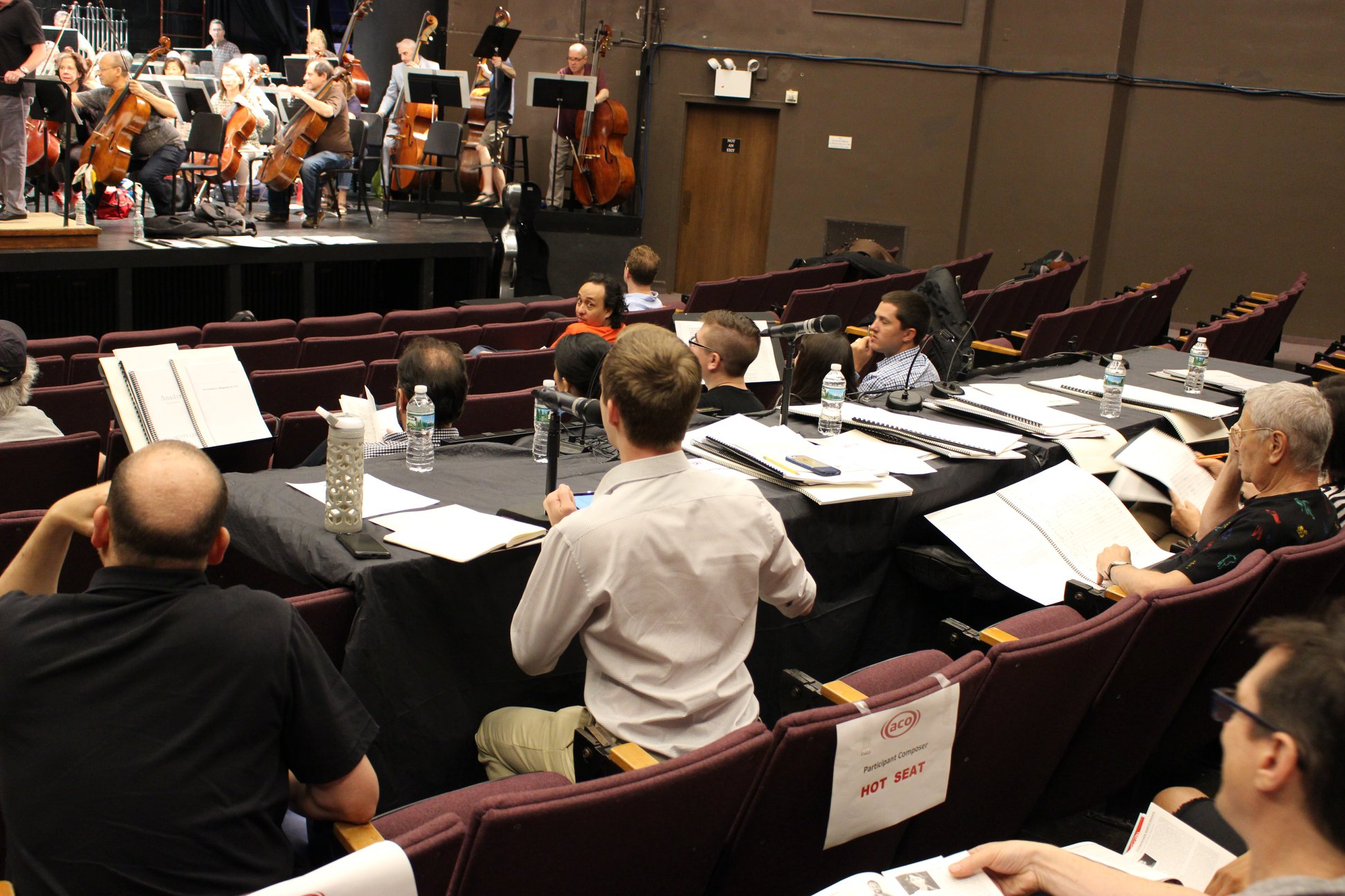 """One of the Underwood composers sitting in a seat marked """"hot seat"""" while the American Composers Orchestra reads through his music. (Photo by Peter Yip, courtesy Jensen Artists)"""