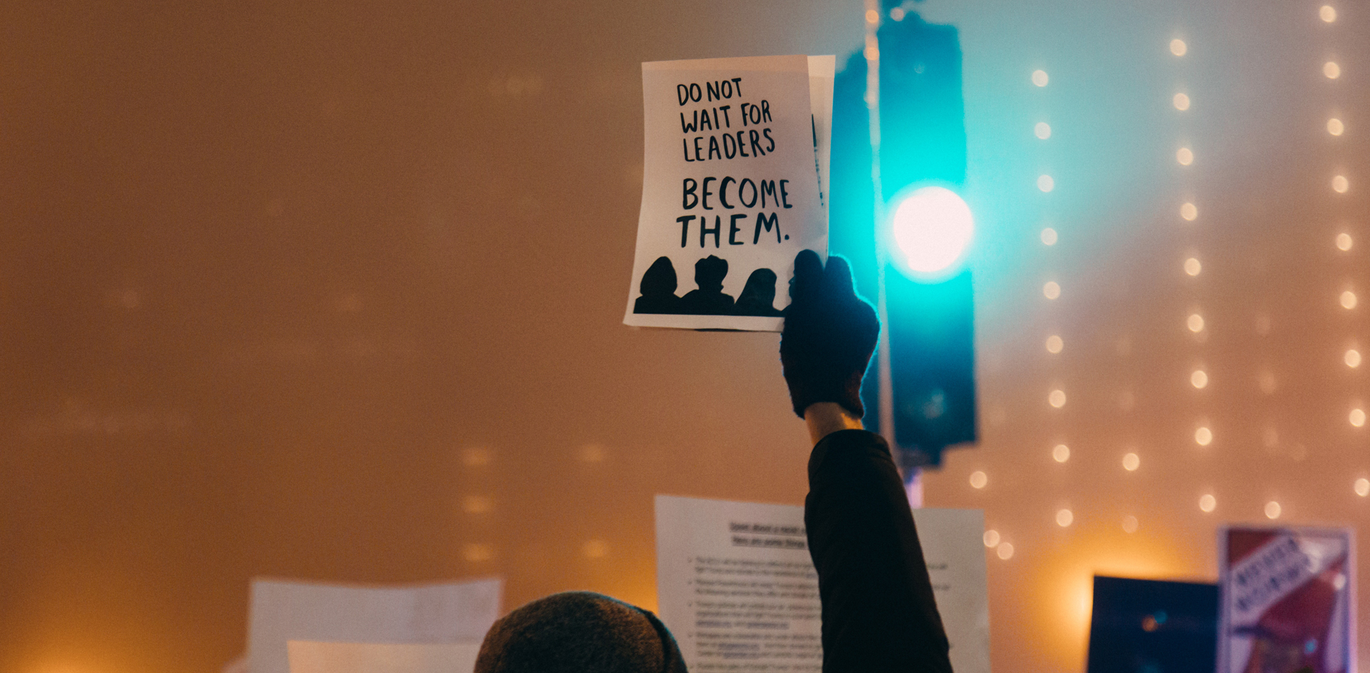 """A woman with a gloved hand holding a paper that says """"DO NOT WAIT FOR LEADERS - BECOME THEM."""" (Photo by rob walsh on Unsplash)"""