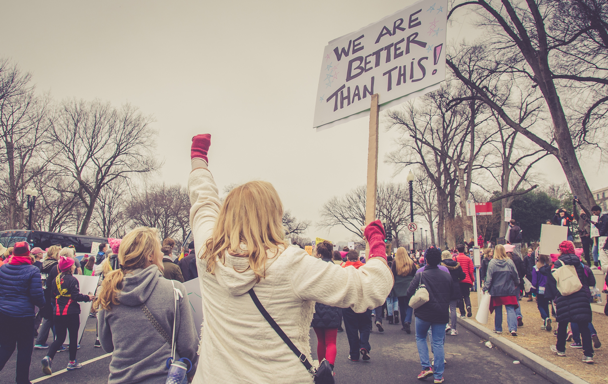"""Women holding picket sign reading """"We Are Better Than This"""" marching with many other women."""