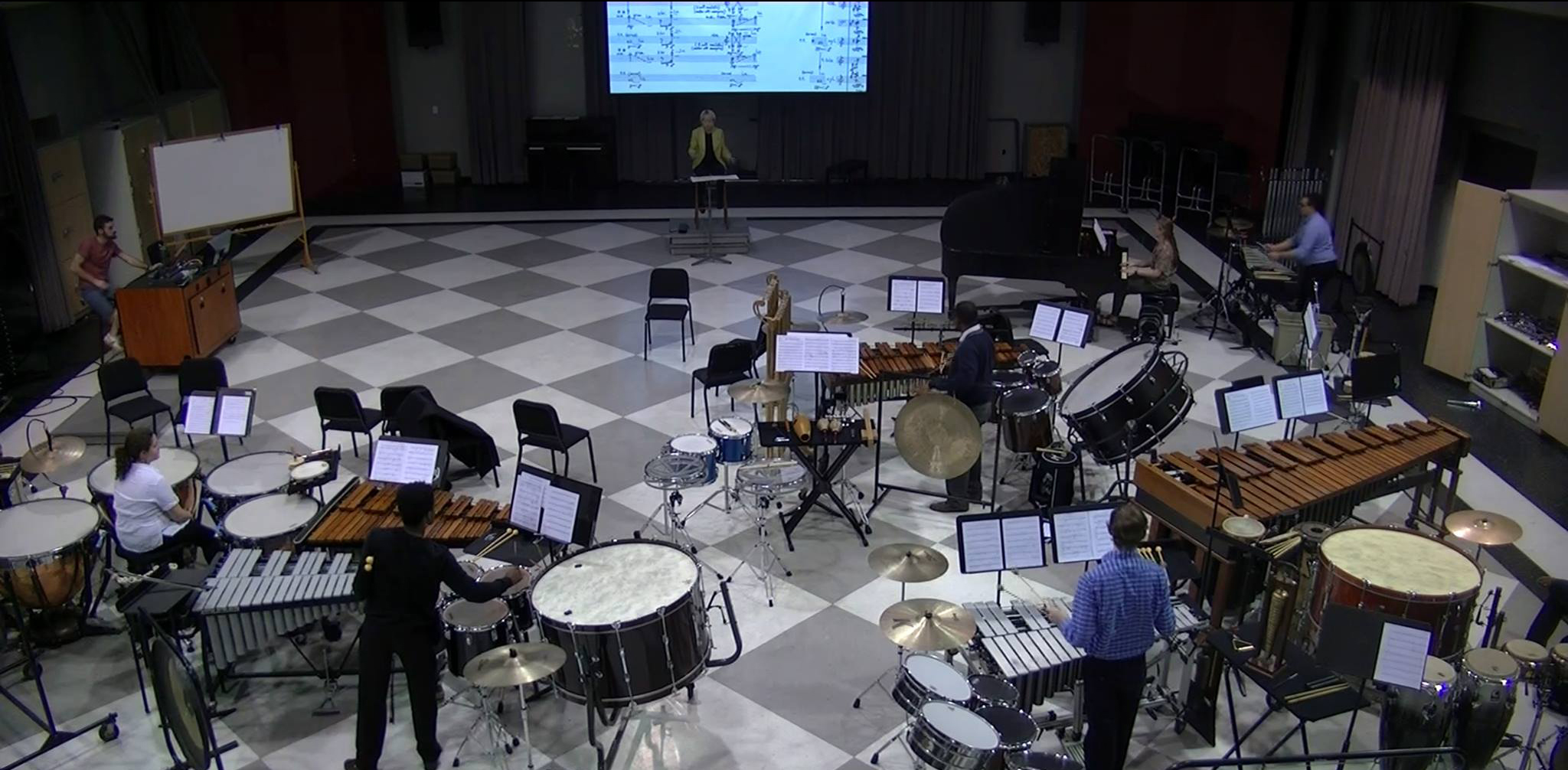 Cynthia Johnston Turner leading a band rehearesal with a score projected on an LED screen in back of her.