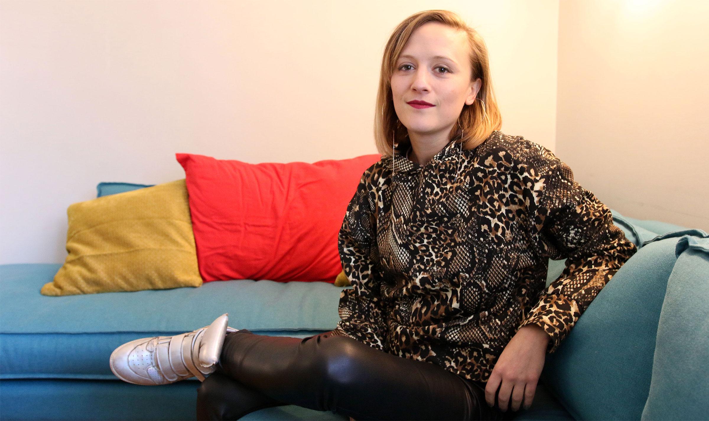Ellen Reid sitting on a couch.