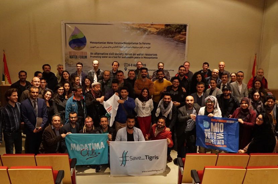 Over 50 people gathered in a room in front of a banner for the Mesopotamian Water Forum