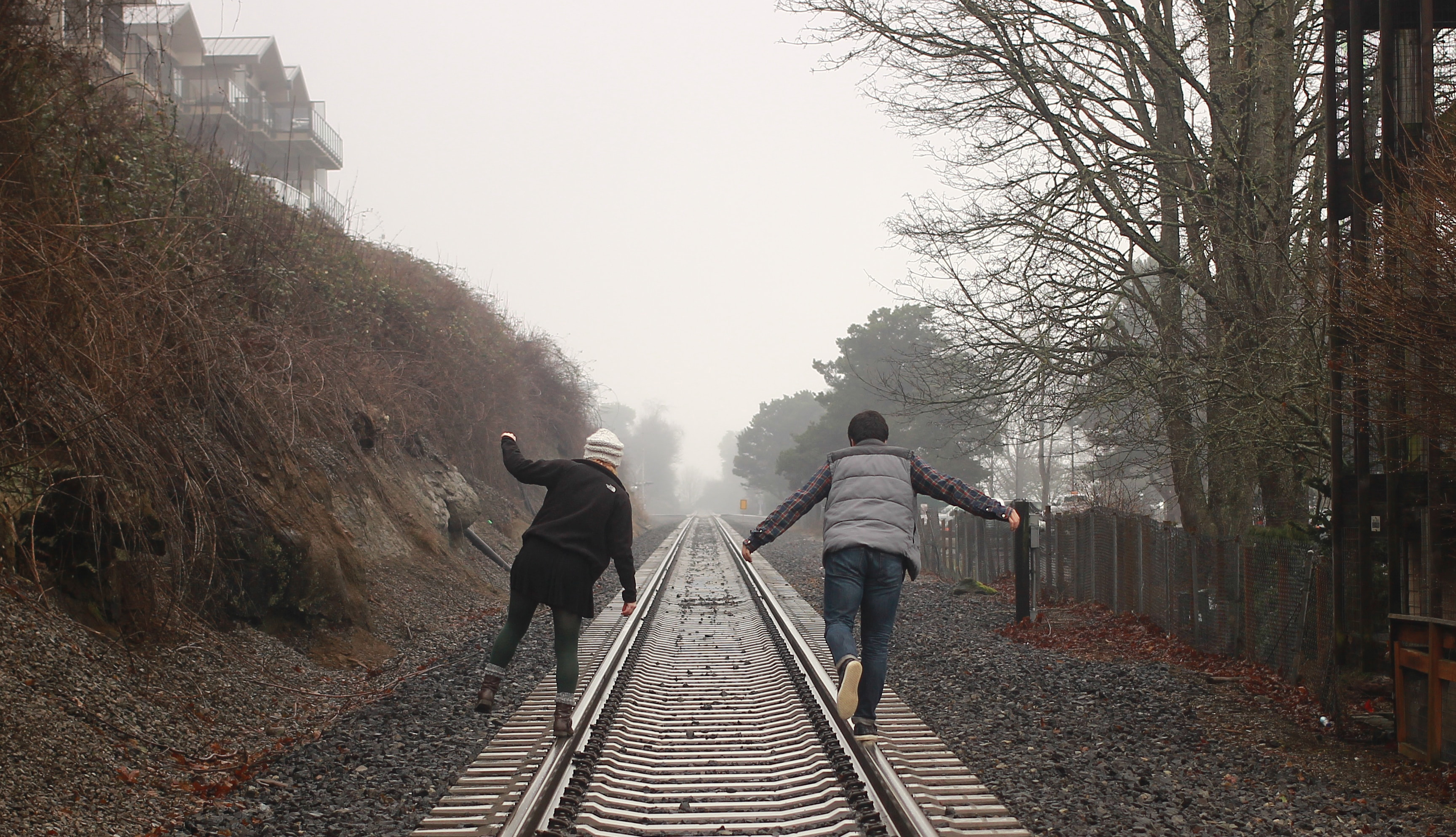 Two people photographed from the back walking on the left and right rails of traintracks in the country.