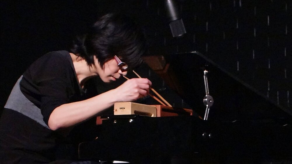 Ju-Ping Song at a toy piano with chopsticks
