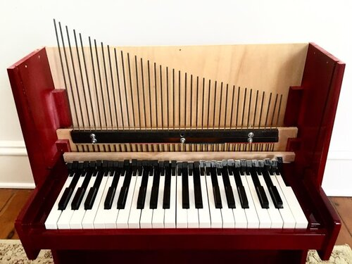 An open toy piano with all the tines exposed.