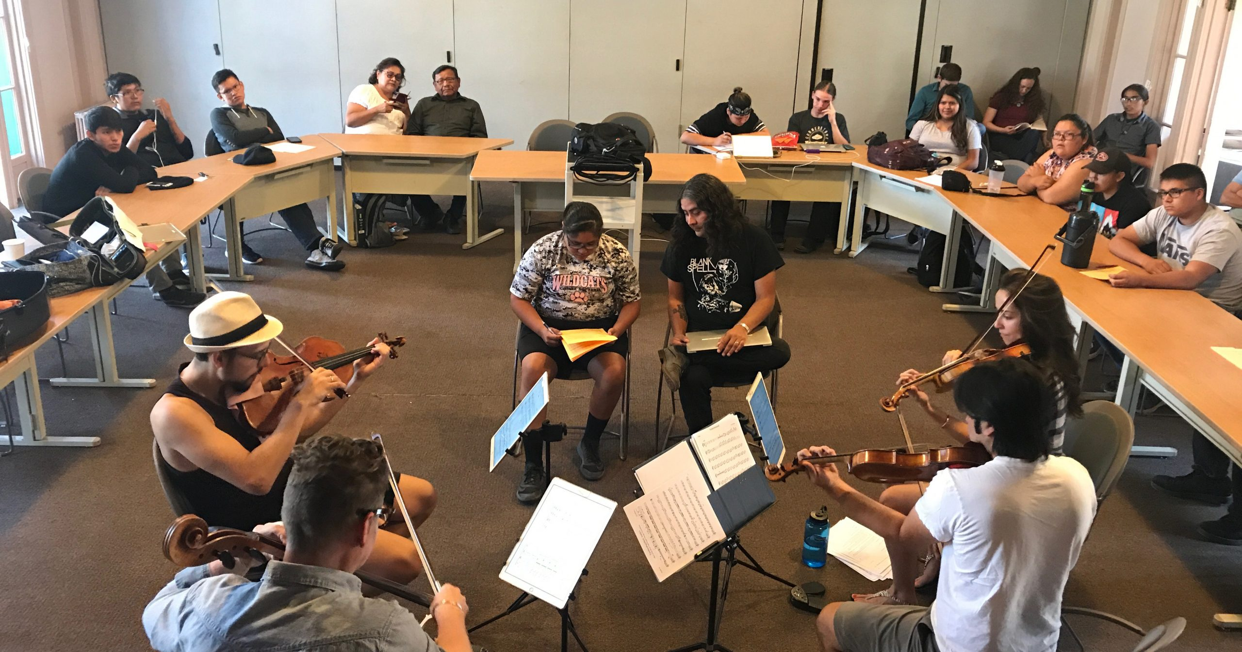 The four musicians of a string quartet, a composer and a mentor sit in the middle of a circle surrounded by students