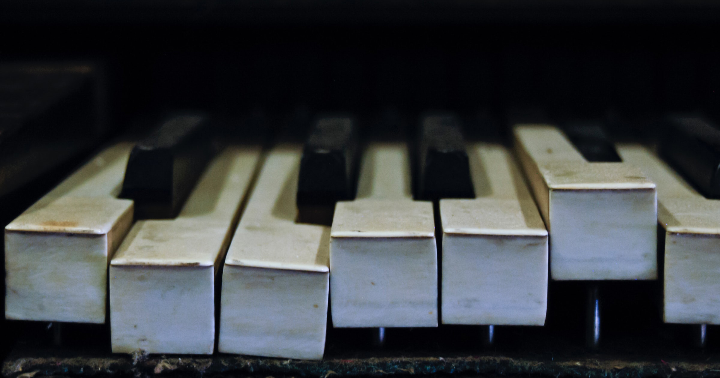 A close up of a piano keyboard with broken/warped keys going in various directions.