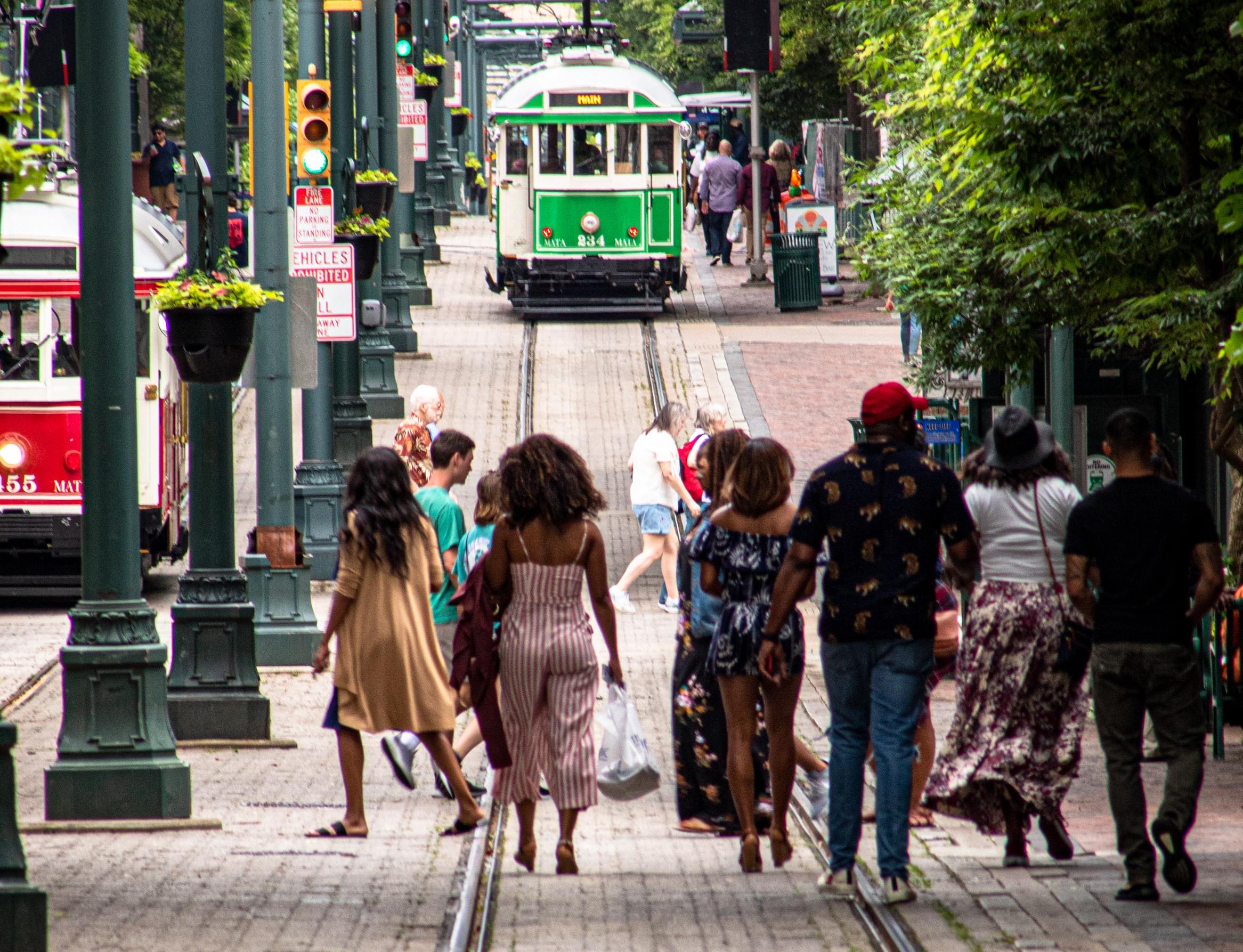 People walking on the tracks toward a streetcar in Memphis, TN, (Photo by Joshua J. Cotten / Unsplash)