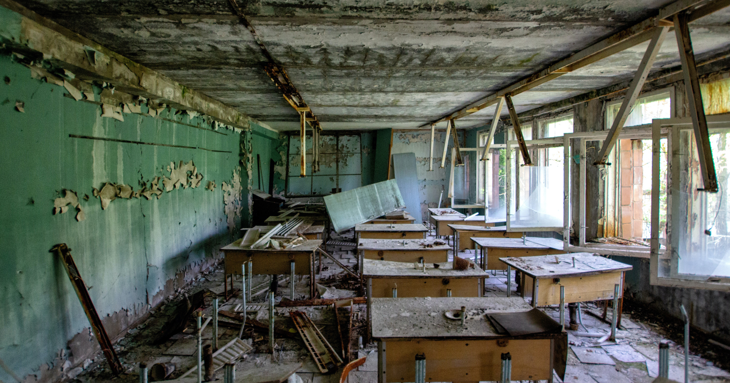 A photo of a wrecked classroom with paint peeling from the ceiling, desks turned over and broken.
