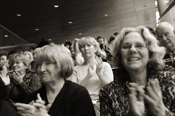Audience members in a concert hall applauding