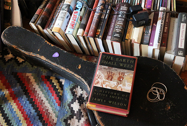 A pile of books on the floor, one (The Earth Shall Weep - A History of Native America) on top of a banjo case