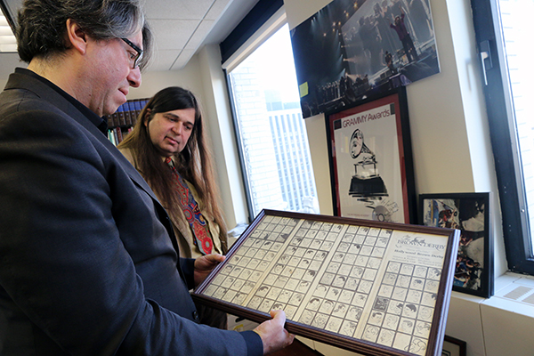 Wachner holds framed memorabilia as FJO looks on.