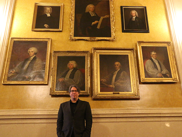 Wachner standing in front of seven framed portraits on a wall.