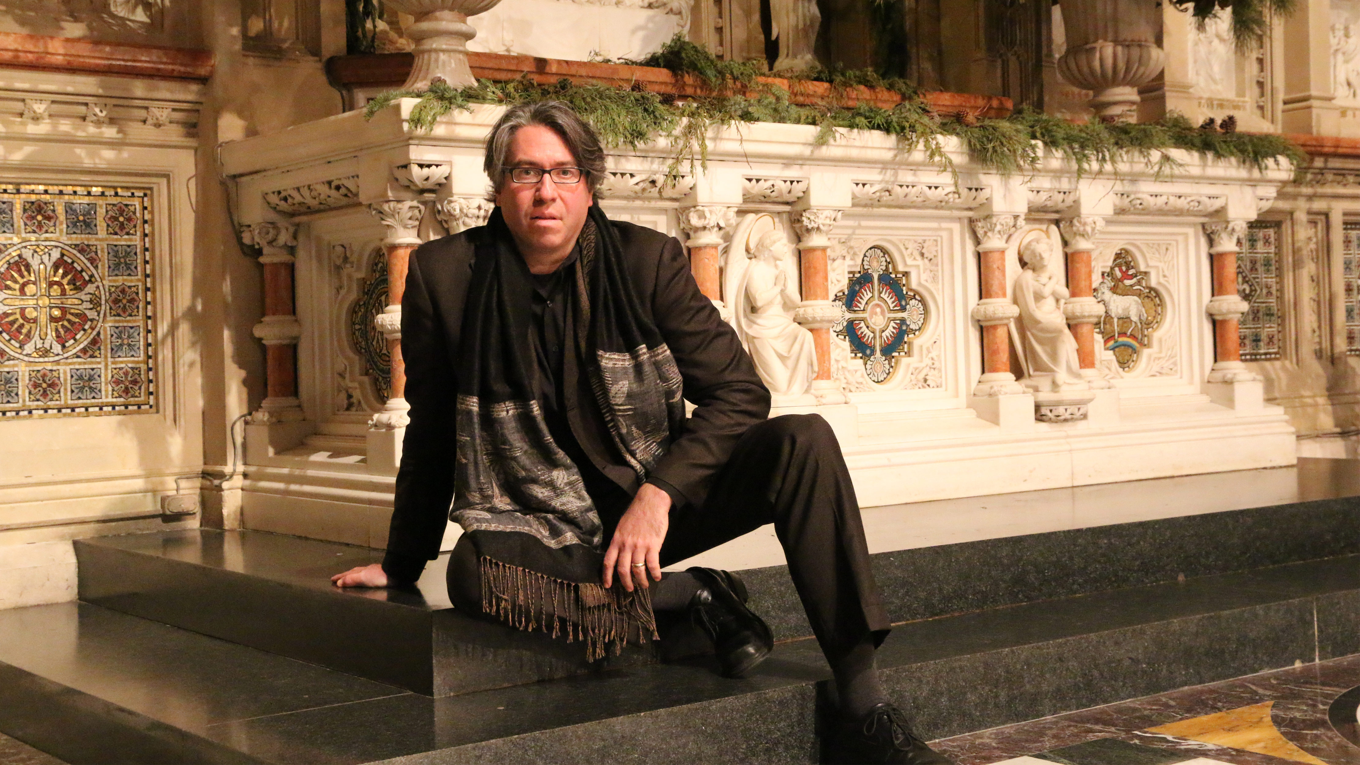 Julian Wachner sitting in front of Trinity Wall Street altar.