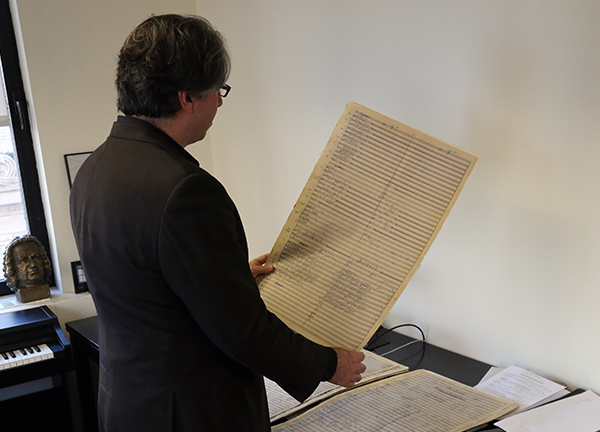 Wachner holding a page of music manuscript with a electric keyboard and a bust of J.S. Bach on top  to his left.