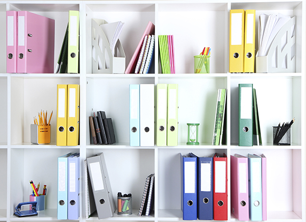 White office shelves with folders and different stationery, clos