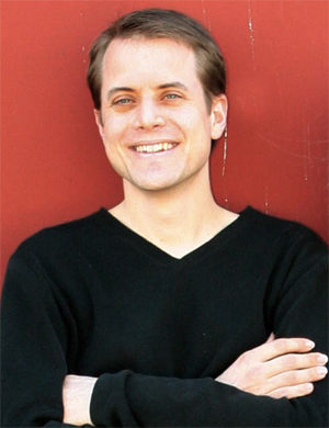 Bradley Colten in a black shirt smiling against a red background.