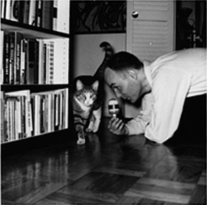 Dockstader on floor near bookcase holding a microphone near a cat walking by