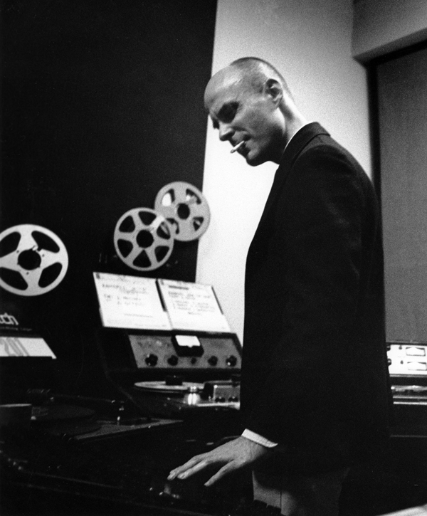 Dockstader working at a reel-toreel tape console standing up and smoking a cigarette