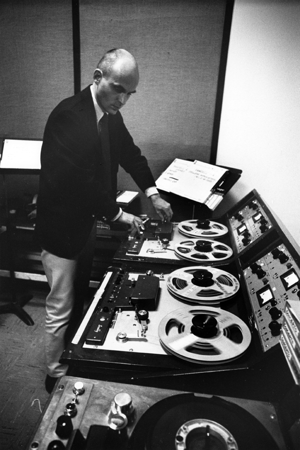 Dockstader manipulating magnetic tape at a reel-to-reel console