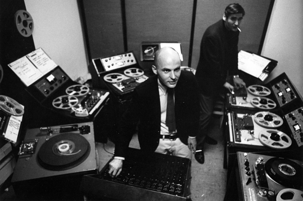 Jim Reichert standing in back operating one of many reel-to-reel tape machines and Tod Dockstader sitting in front of a console turning a knob.