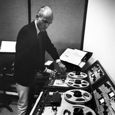 Tod Dockstader manipulating magnetic tape at a reel-to-reel console in a studio