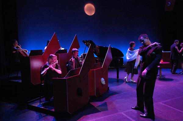 Members of the Pittsburgh New Music Ensemble in a staged performance with dancers and a projected image of the moon