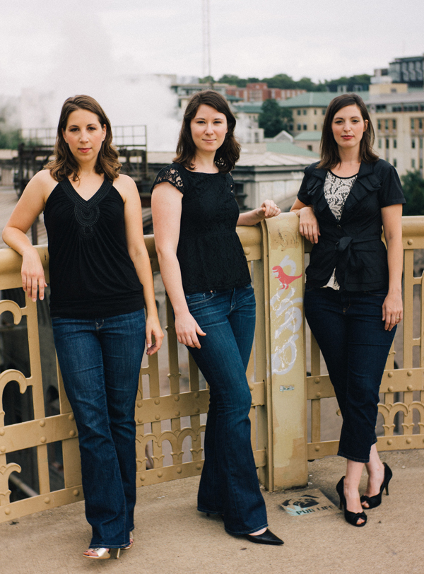 The three members of the Trillium Ensemble: standing and leaning on a fence.