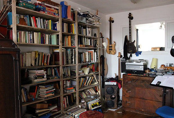 Shelves crammed full of books and various electric guitars hanging on a wall