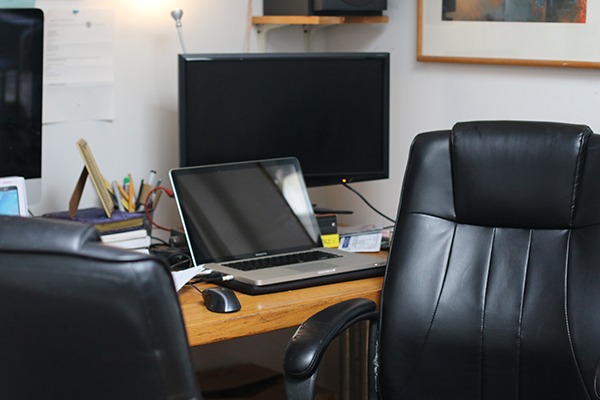A laptop computer with a larger monitor in back on an office table in back of an office chair
