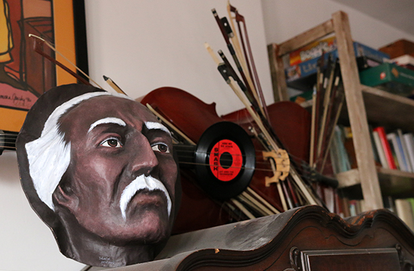 sculpture made from a broken cello, various bows, 45rpm records, and a head.