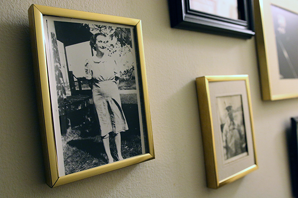 A wall with old portrait photographs in frames