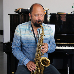 Hafez Modirzadeh playing his alto saxophone sitting on a piano bench in front of an upright piano.