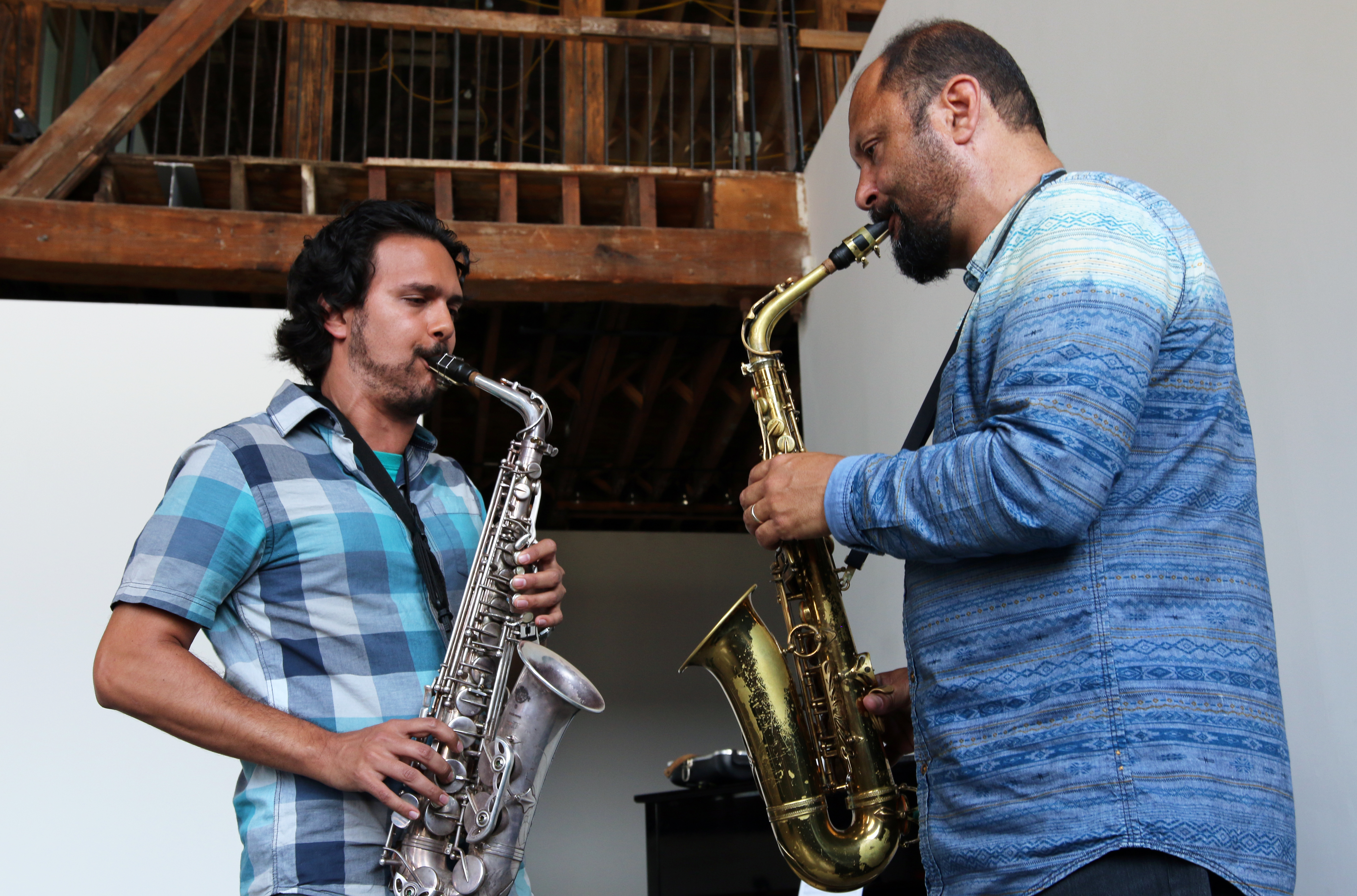 Aakash Mittal and Hafez Modirzadeh facing each other playing alto saxophones.