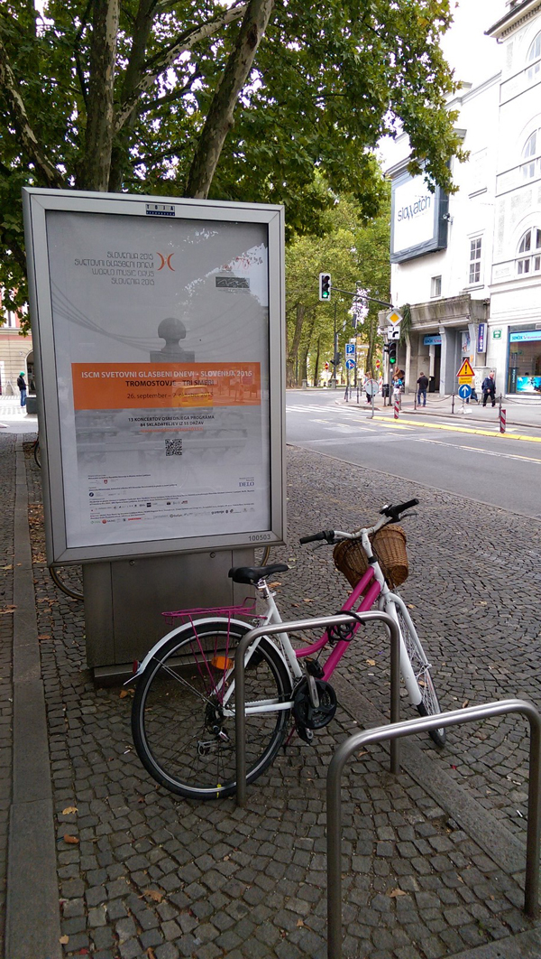 A bicycle parked in front of a poster for the 2015 ISCM World Music Days on a street in Ljubljana.