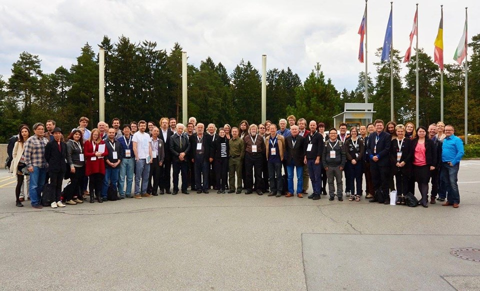 Delegates for the ISCM World Music Days stand together with flags and trees in the background.