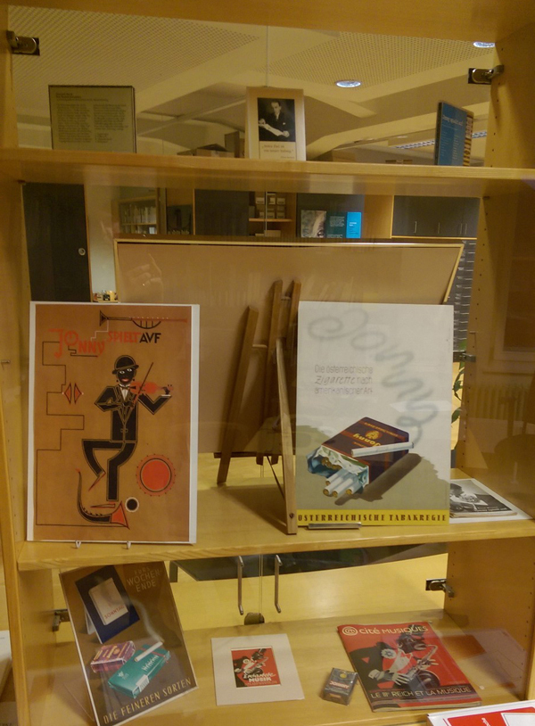 A memorabilia diplay case showing posters, a pack of cigarettes and other items related to Ernst Krenek's opera Jonny spielt auf.