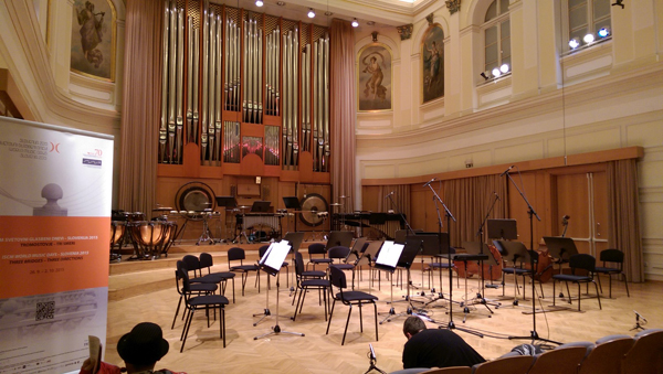 The stage of Kozina Hall showing some instruments, chairs, and (on the back wall) organ pipes.