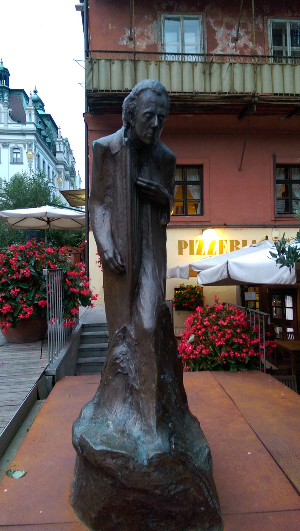 A statue of the composer Gustav Maher in front of a pizzeria.