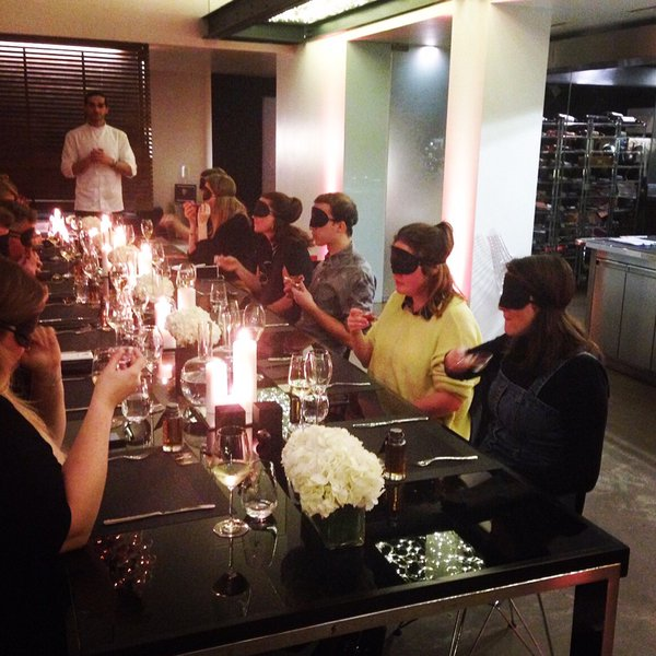 Blindfolded patrons sit around a table and eat various food items, smell perfume, and listen to music.