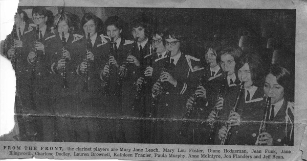 A reproduction of photo from a newspaper of 12 uniformed young people playing clarinets.